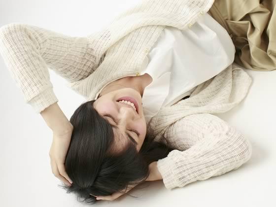 頭を抱えて寝転がるほど悩む女性