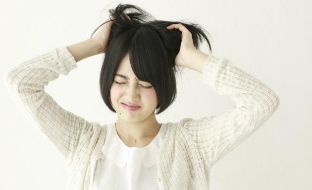 頭をかきむしる若い女性