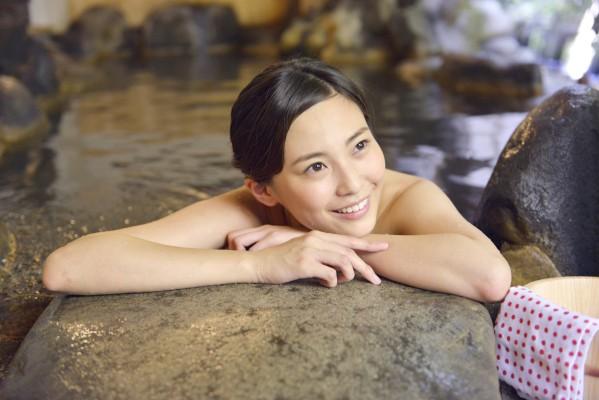 温泉に浸かる若い女性/イメージ