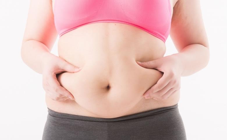 お腹の脂肪を握る女性